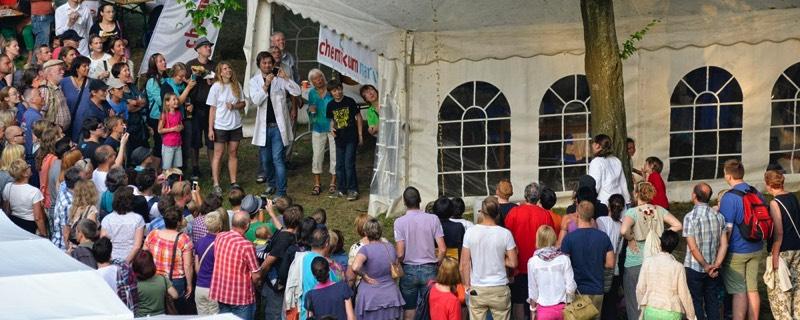 Besucher schauen beim Experimentieren vor dem Chemikum Zelt zu.